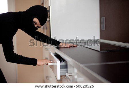 thief in black clothes and balaclava robbed home - stock photo