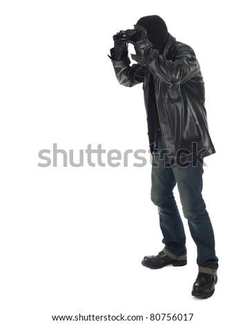 thief in black clothes and balaclava using binoculars - stock photo