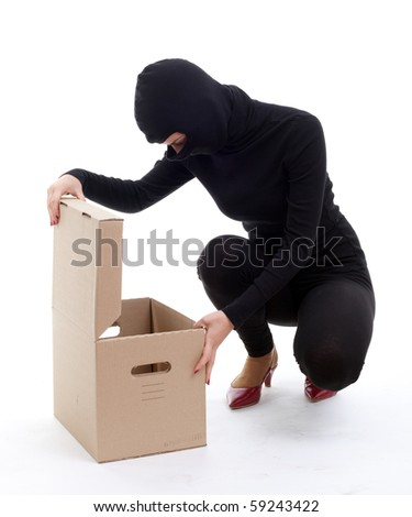 thief in black clothes and balaclava with box - stock photo