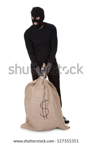 Thief in black clothes wearing a balaclava carrying a large bag of money with a dollar sign isolated on white - stock photo