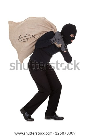Thief in black clothes wearing a balaclava carrying a large bag of money with a dollar sign over his shoulder isolated on white - stock photo