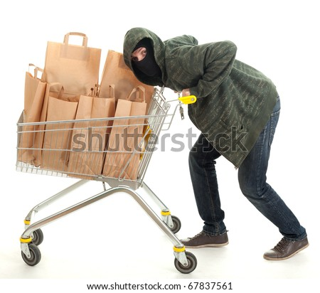 thief in dark clothes and balaclava with shopping cart full of papers bags - stock photo