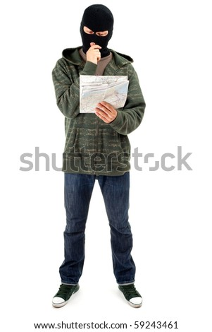 thief in dark clothes and black balaclava with map - stock photo