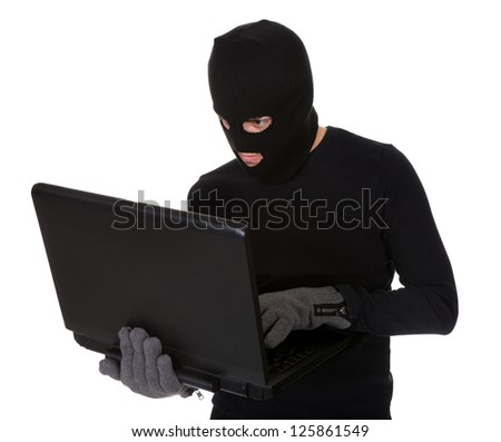 Thief in disguise stealing data from computer - stock photo
