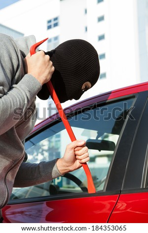 Thief in hooded jacket and balaclava opening car's door with crowbar - stock photo
