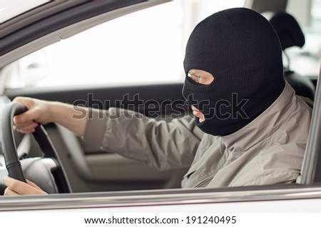 Thief in mask steals expensive new car. - stock photo
