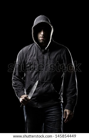 Thief in the hood on a black background - stock photo