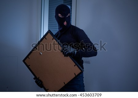 Thief inside home  stealing a painting from the wall - stock photo