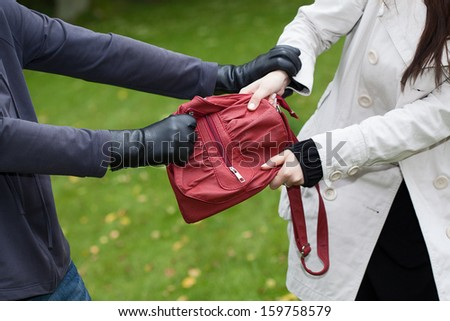 Thief is assaulting a girl to steal a handbag - stock photo