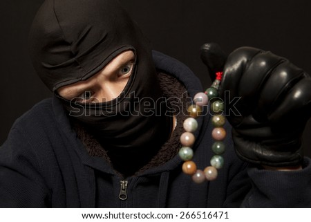 Thief. Man in black mask with a jade necklace. Focus on thief - stock photo