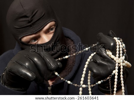 Thief. Man in black mask with a pearl necklace. Focus on pearl necklace - stock photo