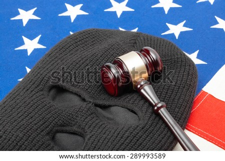Thief mask with judge gavel over US flag