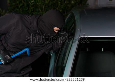Thief preparing to steal a parking car at night.