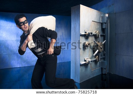 thief running out of a bank vault, low-key photo - stock photo