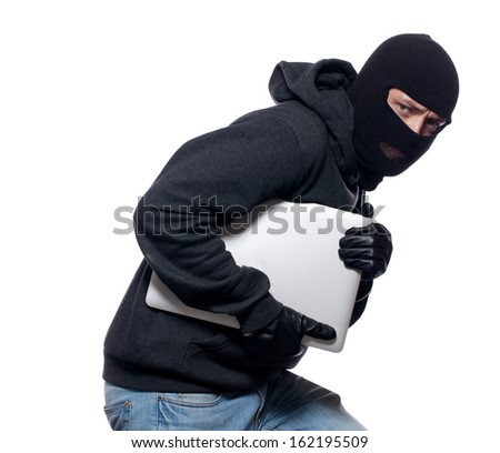 Thief stealing a laptop computer - stock photo