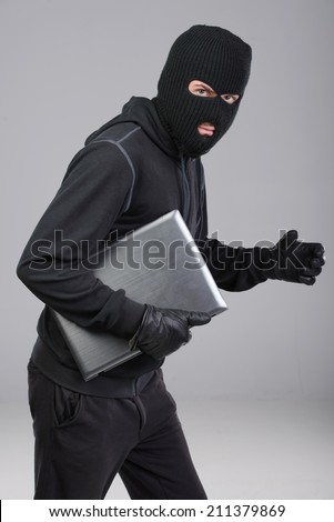 Thief stealing a laptop computer. Isolated on gray background - stock photo