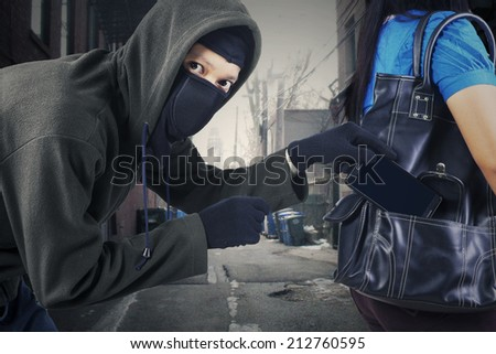 Thief stealing a mobile phone from handbag of a woman on the street - stock photo