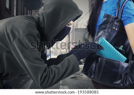 Thief stealing a wallet from handbag of a woman on the street - stock photo
