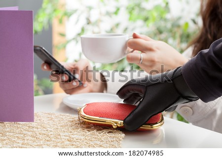 Thief stealing a wallet in coffee shop - stock photo