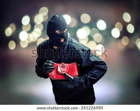 Thief stealing a womans handbag in a city street concept for crime, pickpocketing and security - stock photo