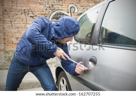 thief stealing automobile car  in the city street - stock photo