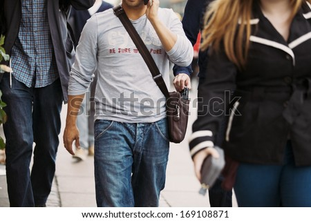 Thief stealing wallet from man's handbag while he's talking on the mobile phone. Pickpocketing on the street during daytime - stock photo
