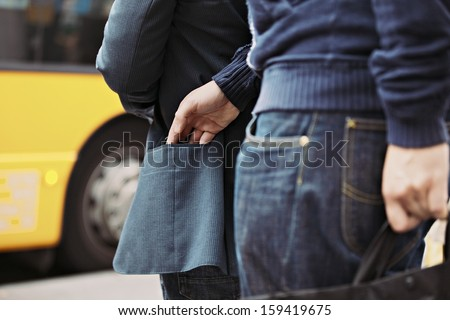 Thief stealing wallet of a man walking on the street. Pickpocketing on the street during daytime - stock photo