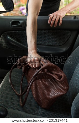 Thief stealing woman's bag from car, vertical - stock photo