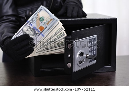 Thief steals dollars from the safe, close up - stock photo