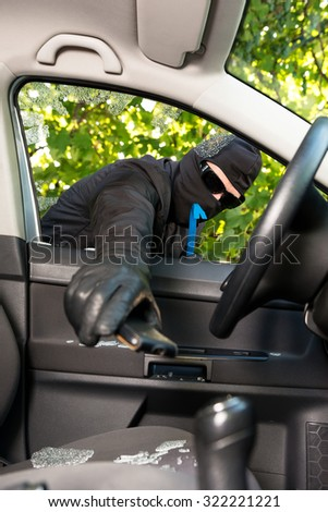 Thief successfully breaking a vehicle's window.