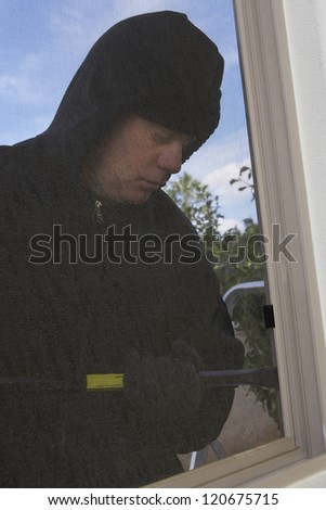 Thief trying to open the window with crowbar
