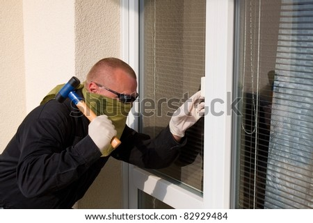 thief with a hammer smashing a glass door - stock photo