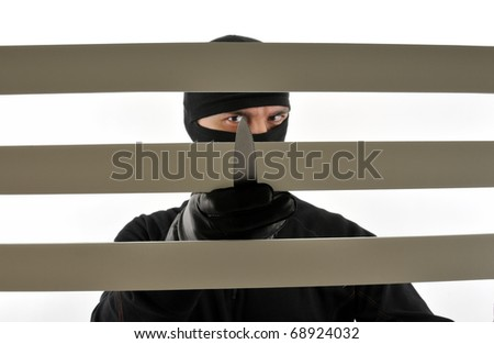 Thief with a knife looking through the window. - stock photo