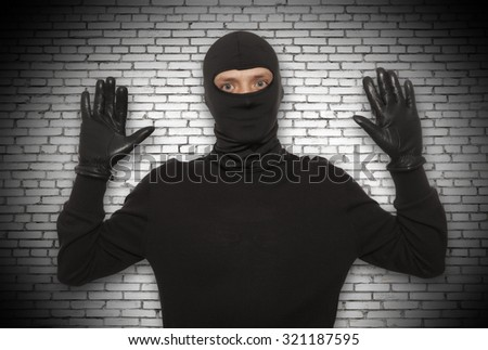 Thief with balaclava caught in front of the wall - stock photo