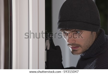 thief with crowbar breaking into a house by night - stock photo