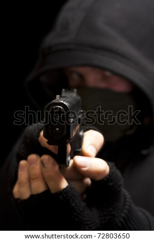 Thief with gun aiming into a camera - isolated on black background - stock photo