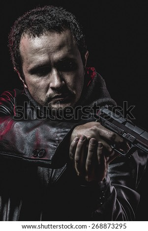 thief with gun in hand. man in leather jacket - stock photo