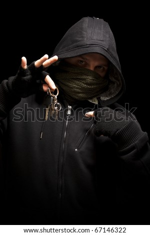 Thief with keys aiming into a camera - isolated on black background - stock photo