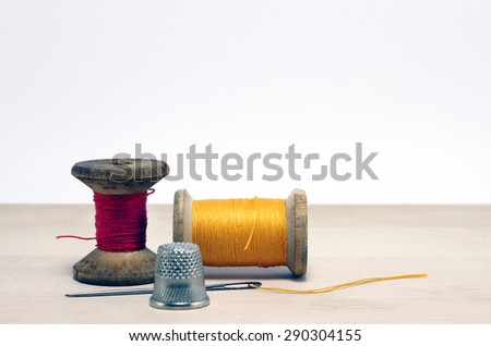 thimble and needle.Old spool of thread with needle closeup. Tailor's work table. textile or fine cloth making. - stock photo