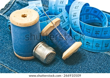 thimble, meter and spools of thread on denim - stock photo