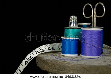 thimble on spool of thread with scissor and tape measure - stock photo