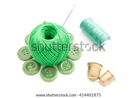 thimbles, needles, green buttons and thread closeup on white - stock photo
