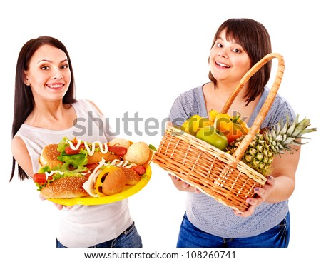 Thin and big women choosing between fruit and hamburger.