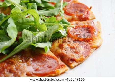 thin and crisp homemade pizza with pepperoni and fresh arugula - stock photo
