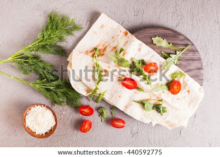 Thin armenian pita bread, cherry tomatoes, cheese, arugula and herbs for backing