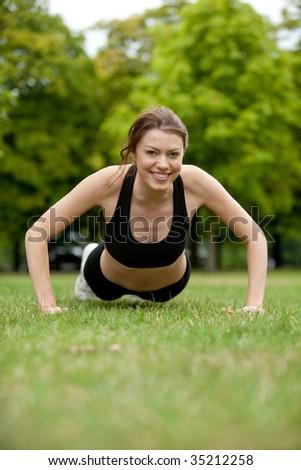 Thin athletic woman doing push-ups at a park - stock photo