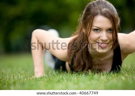 Thin athletic woman doing push-ups at the park - stock photo