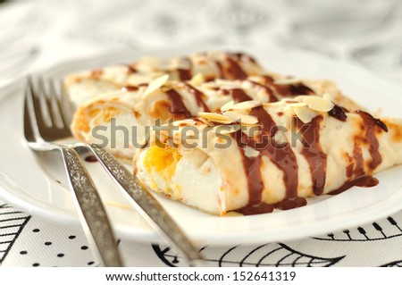 Thin crepes filled with orange curd cream topped with chocolate sauce and almond flakes - stock photo
