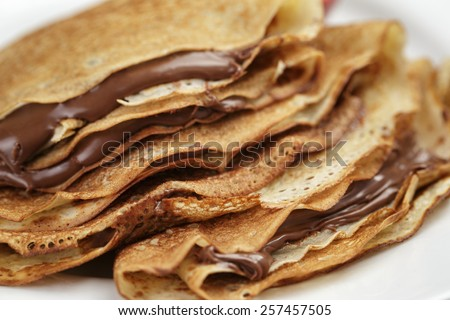 thin crepes or blinis with chocolate cream on plate - stock photo
