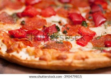 thin crust pepperoni pizza with red peppers on a pizza stone - stock photo